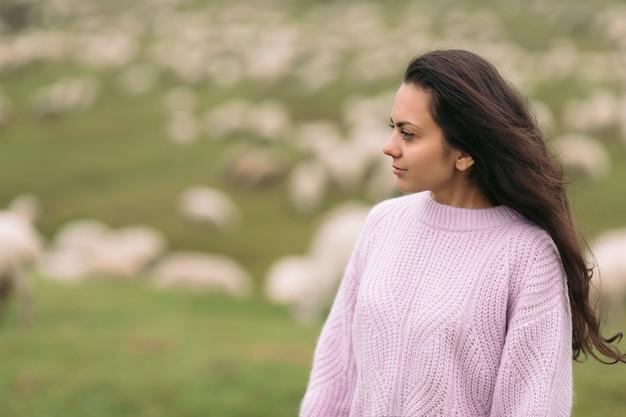 Portret van een jonge vrouw in een trui tegen kuddes schapen in de bergen in mistige dag