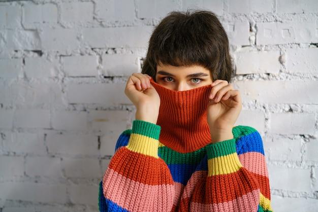 Portret van een jonge vrouw in een veelkleurige trui, die haar gezicht bedekt met een trui. het concept van verlegenheid