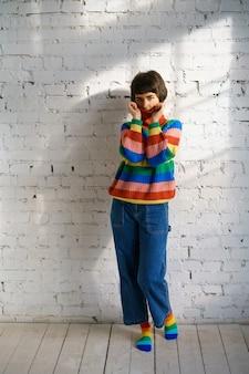 Portret van een jonge vrouw in een veelkleurige trui, die haar gezicht met een trui. het concept van verlegenheid