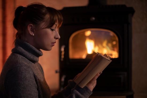 Portret van een jonge vrouw in een warme trui thuis bij de open haard een boek lezen