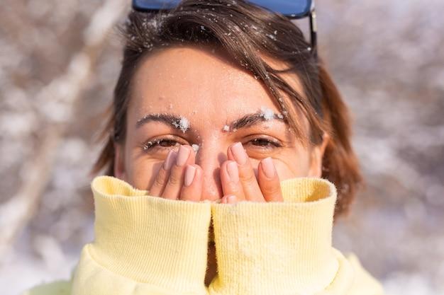 Portret van een jonge vrouw in een winterbos op een zonnige dag met een sneeuwwitte glimlach, gek rond