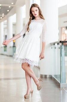 Portret van een jonge vrouw in een witte korte jurk