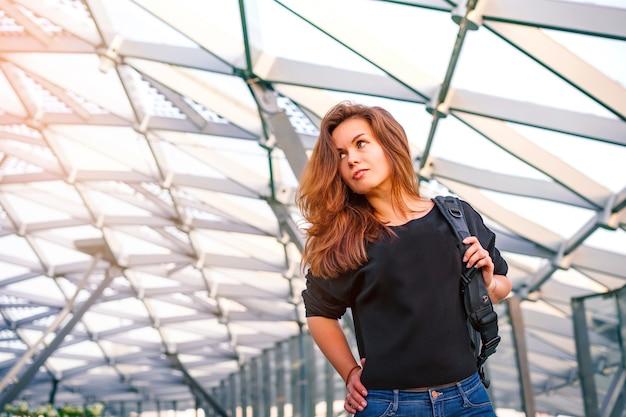 Portret van een jonge vrouw in een zakencentrum met een glazen plafond in de vorm van een honingraat