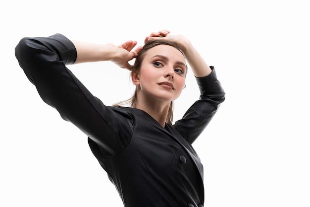 Portret van een jonge vrouw in een zwart lederen jurk die zich voordeed op een witte achtergrond