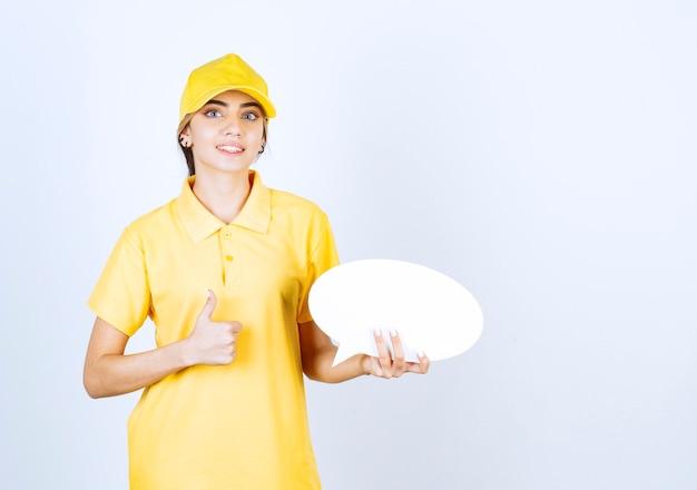 Portret van een jonge vrouw in geel uniform met een lege lege tekstballon met een duim omhoog.