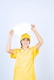 Portret van een jonge vrouw in geel uniform met een lege lege tekstballon.