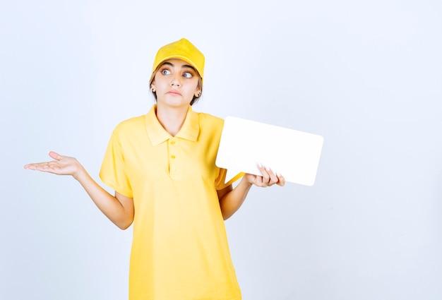 Portret van een jonge vrouw in geel uniform met een lege tekstballon.