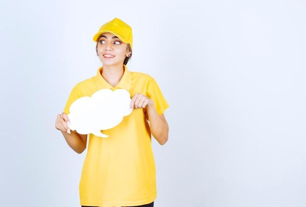 Portret van een jonge vrouw in geel uniform met een lege witte tekstballonwolk.