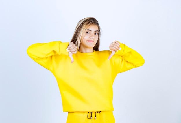 Portret van een jonge vrouw in gele outfit die duimen naar beneden geeft
