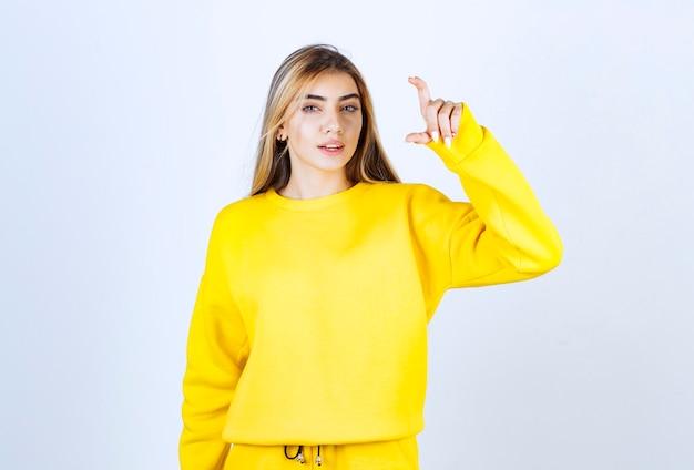 Portret van een jonge vrouw in gele outfit poseren en staan