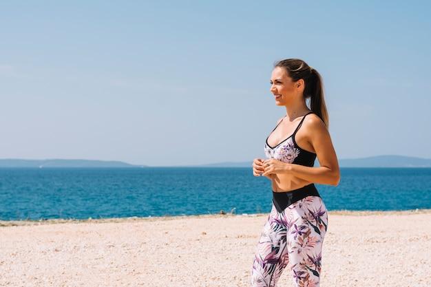 Portret van een jonge vrouw in geschiktheidsslijtage die zich dichtbij het strand bevinden