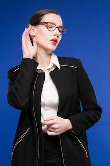 Portret van een jonge vrouw in glazen en jas
