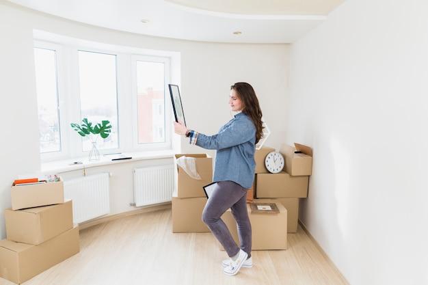 Portret van een jonge vrouw in haar nieuwe huis kijken naar foto frame