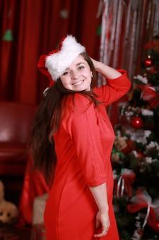 Portret van een jonge vrouw in helper kerstmuts en rode jurk ter voorbereiding op kerstmis thuis. kerstmis, kerstmis, winter, geluksconcept - glimlachende vrouw op de boommuur van de kerstmisglans.