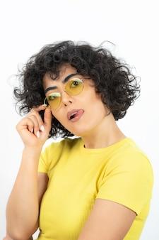 Portret van een jonge vrouw in het geel die een bril draagt