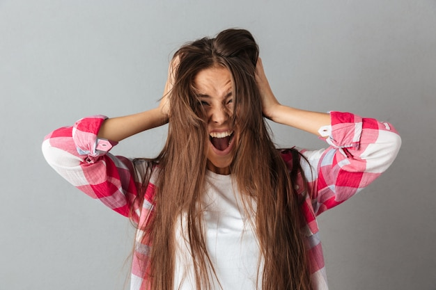 Portret van een jonge vrouw in het geruite overhemd gillen