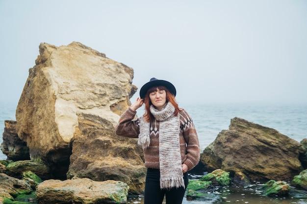 Portret van een jonge vrouw in hoed op een rots tegen een prachtige zee