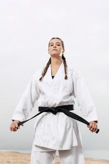 Portret van een jonge vrouw in karate kostuum