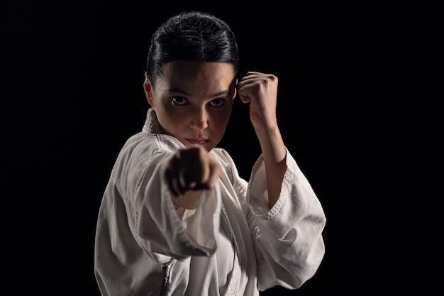 Portret van een jonge vrouw in kimono in gevechtshouding die naar de camera kijkt