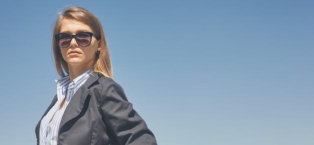 Portret van een jonge vrouw in korte kokerjasje die zonnebril draagt