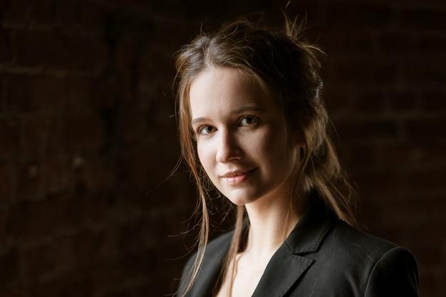 Portret van een jonge vrouw in lingerie en een zwarte jas