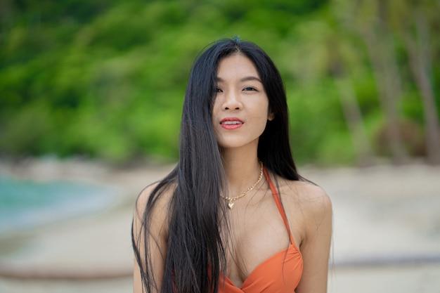 Portret van een jonge vrouw in oranje bikini op tropisch strand