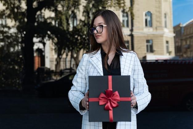 Portret van een jonge vrouw in pak met geschenkdoos in haar handen. stijlvol meisje in glazen houdt cadeau in haar handen.