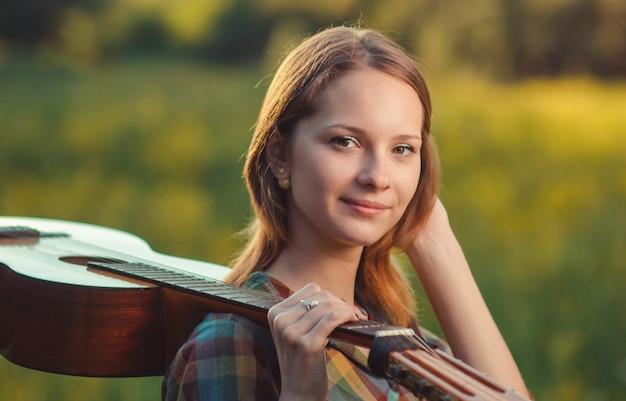 Portret van een jonge vrouw in plaidoverhemd met een akoestische houten gitaar op schouder