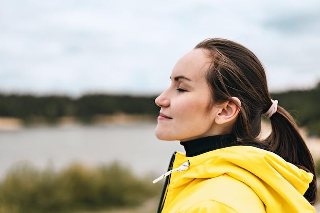 Portret van een jonge vrouw in profiel in de natuur die frisse, schone, koele lucht inademt