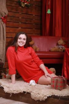 Portret van een jonge vrouw in rode jurk ter voorbereiding op kerstmis thuis.