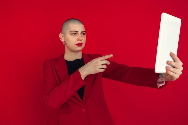 Portret van een jonge vrouw in rood pak die selfie neemt geïsoleerd op rode studio