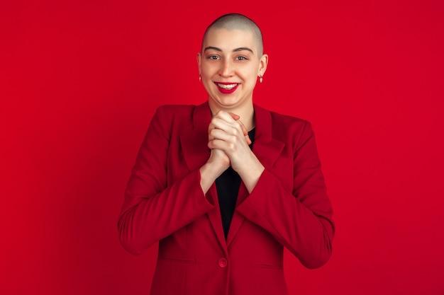 Portret van een jonge vrouw in rood pak geïsoleerd op rode studio