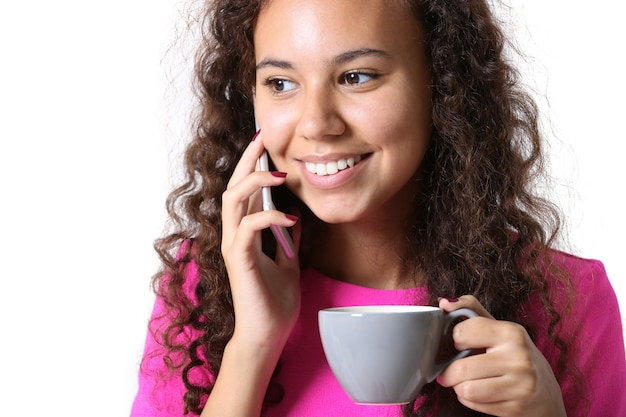 Portret van een jonge vrouw in roze jurk spreken door mobiel met kopje koffie close-up