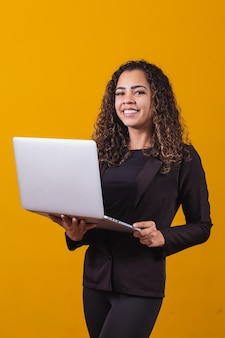 Portret van een jonge vrouw in uitvoerende outfit met laptop op gele achtergrond. zakenvrouw die met laptop werkt. verticaal