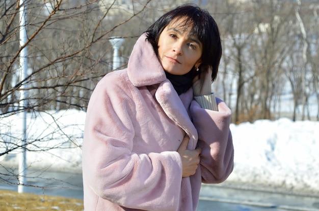 Portret van een jonge vrouw in vacht op een winterse dag