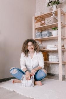 Portret van een jonge vrouw in vrijetijdskleding die prachtig dingen in containers en dozen stopt. het concept van een goede opslag van accessoires en ondergoed in de kast