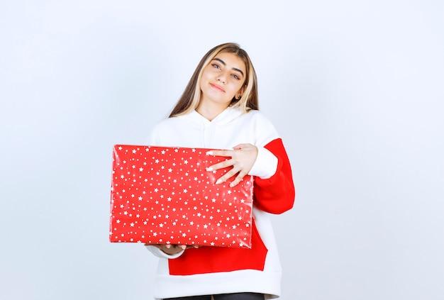 Portret van een jonge vrouw in warme hoodie met kerstcadeau