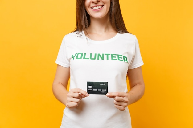 Portret van een jonge vrouw in wit t-shirt met geschreven inscriptie groene titel vrijwilliger houd creditcard geïsoleerd op gele achtergrond. vrijwillige gratis hulp, liefdadigheidswerkconcept.