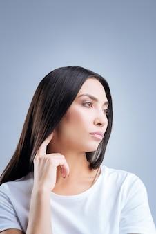 Portret van een jonge vrouw in wit t-shirt poseren tegen een grijze muur