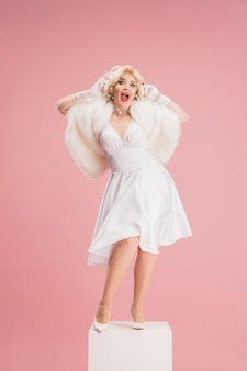 Portret van een jonge vrouw in witte jurk op koraal roze muur vrouwelijk model als een legendarische actrice pin-up concept van vergelijking van tijdperken moderne mode schoonheid