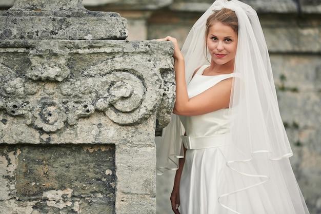 Portret van een jonge vrouw in witte trouwjurk en lange sluier
