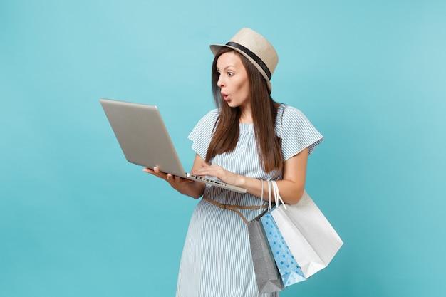 Portret van een jonge vrouw in zomerjurk, strohoed met pakketten met aankopen na online winkelen, met behulp van laptop pc-computer geïsoleerd op blauwe pastelachtergrond. ruimte voor advertentie kopiëren
