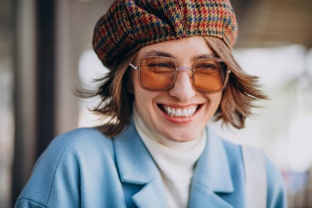 Portret van een jonge vrouw in zonnebril en hoed