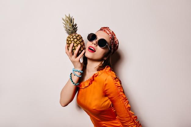 Portret van een jonge vrouw in zonnebril en oranje blouse poseren met ananas op geïsoleerde ruimte.