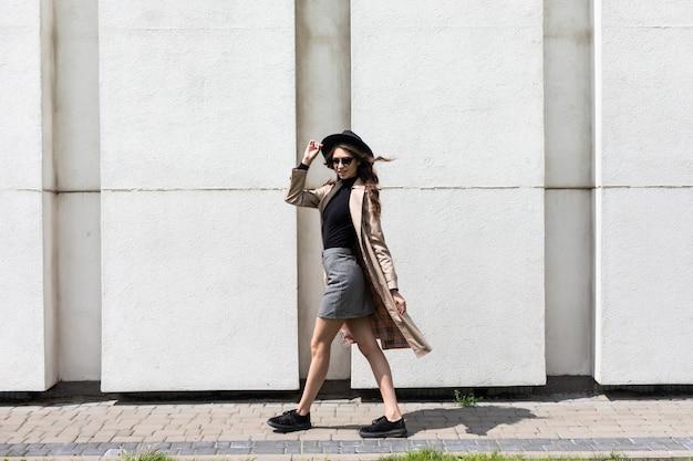 Portret van een jonge vrouw in zonnebril en zwarte hoed die op straat loopt.