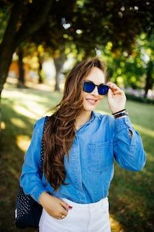 Portret van een jonge vrouw in zonnebril tegen park achtergrondkleur
