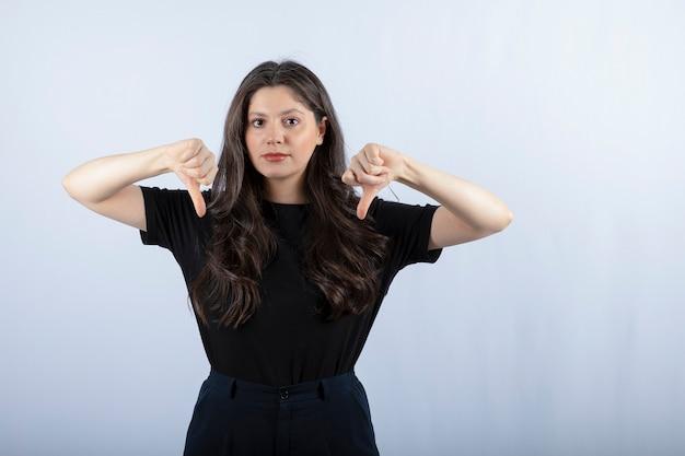Portret van een jonge vrouw in zwarte outfit die duimen naar beneden geeft.