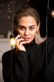 Portret van een jonge vrouw in zwarte trui staan en poseren