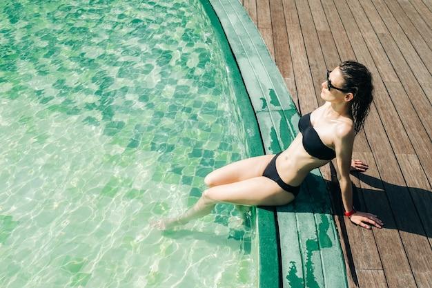 Portret van een jonge vrouw in zwarte zwembroek bij een zwembad
