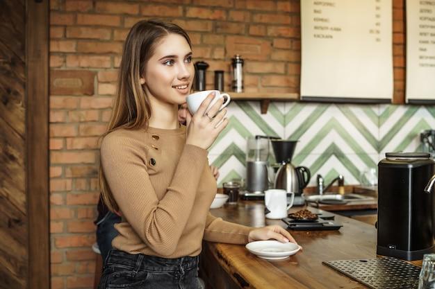 Portret van een jonge vrouw, klant en dame, ner bar zitten geteld en koffie drinken